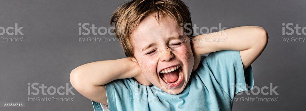 shouting child with red hair and attitude ignoring parents scolding stock photo