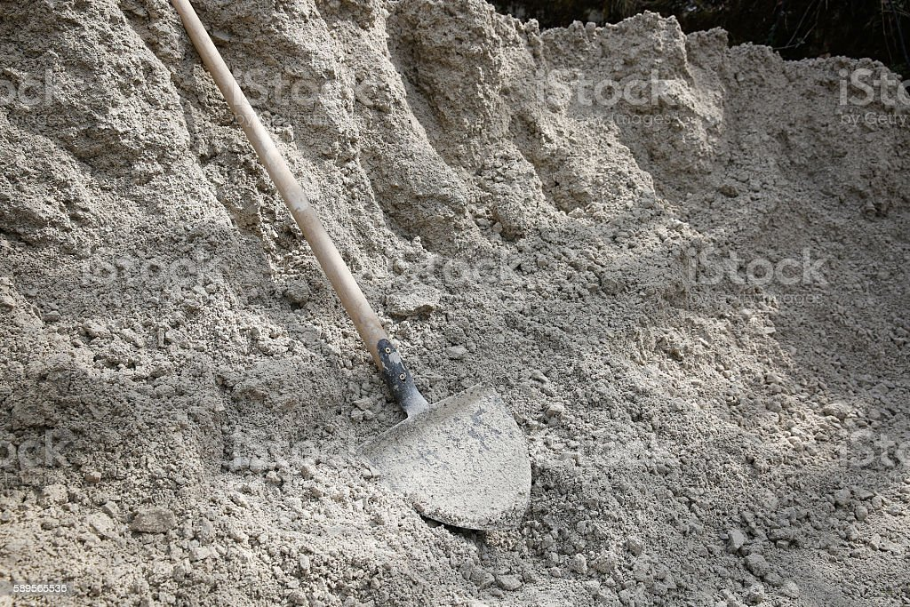 Shovel lying on a pile of construction material stock photo
