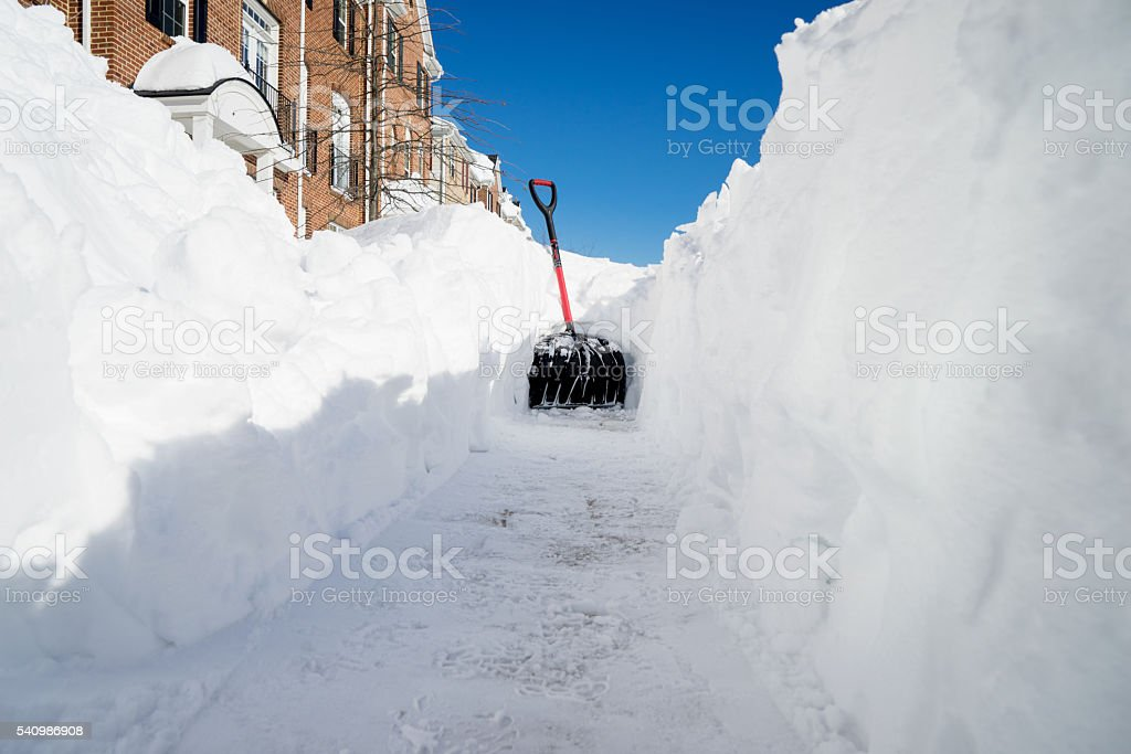 Shovel standing in deep snow stock photo