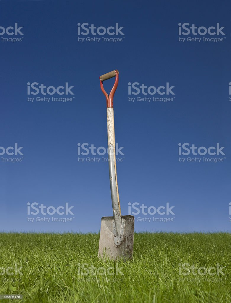 A shovel standing upright in the grass royalty-free stock photo
