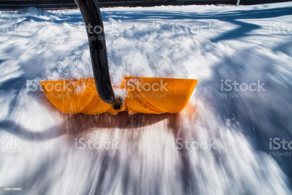 Shoveling snow in motion, pushing stock photo