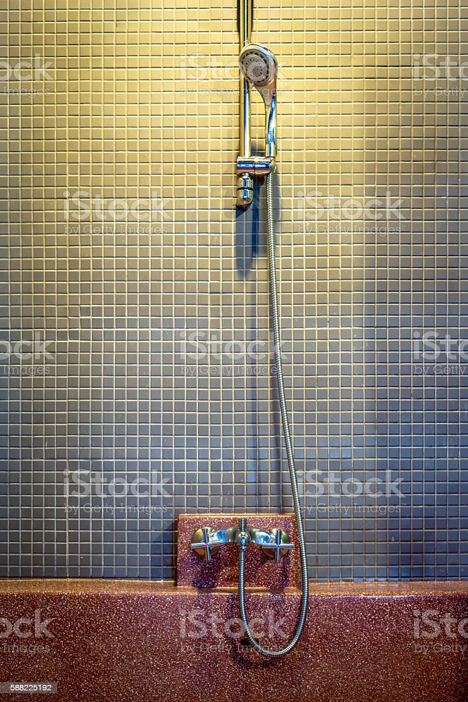 Shower head on ceramic tile wall with empty red bathtub photo libre de droits