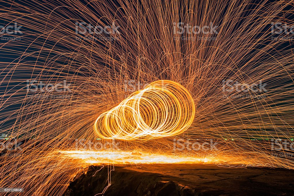 Showers of hot glowing sparks from spinning steel wool stock photo
