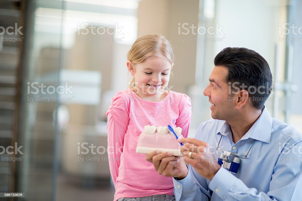 Showing a Girl How to Brush Teeth stock photo