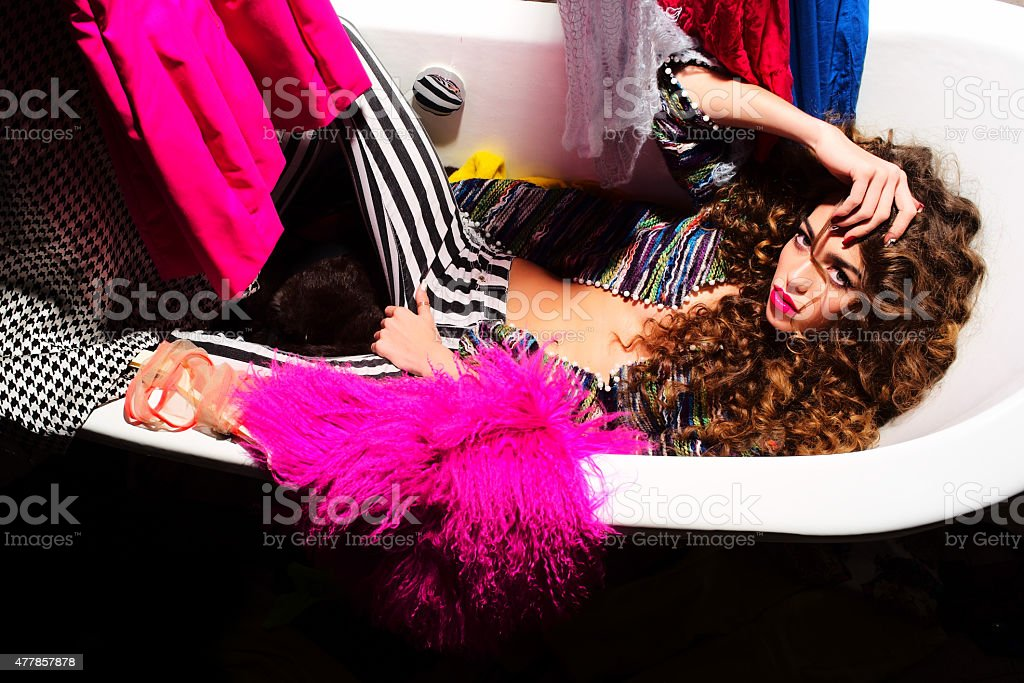 Showy woman in bath with clothes stock photo