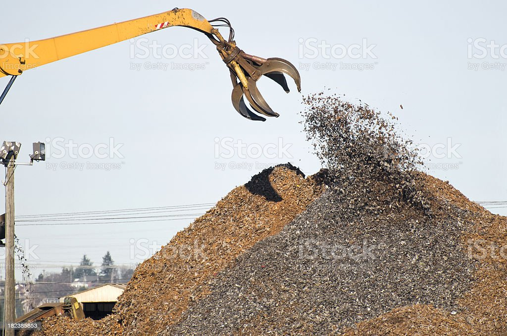 Shredded scrap metal dropped by crane onto pile royalty-free stock photo