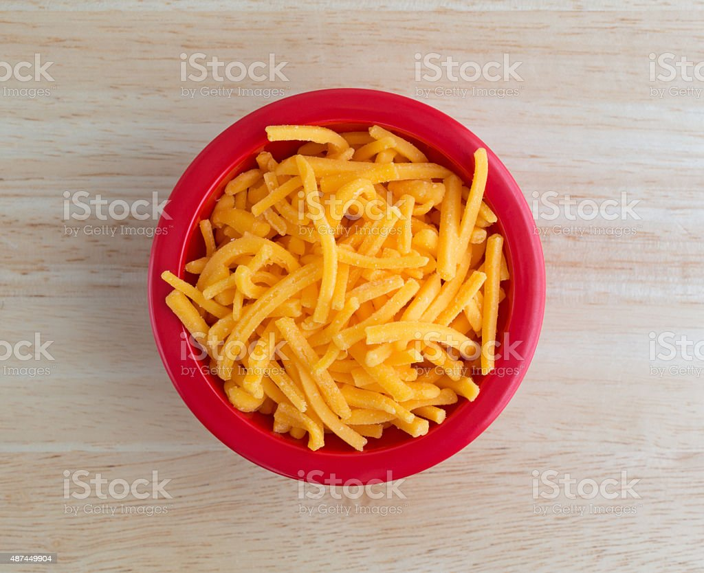 Shredded sharp cheddar cheese in red bowl stock photo