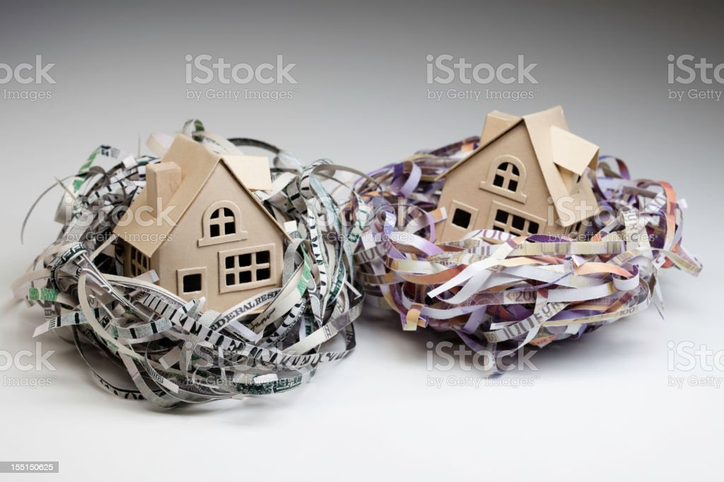 Shredded world currencies wrapped around small houses stock photo