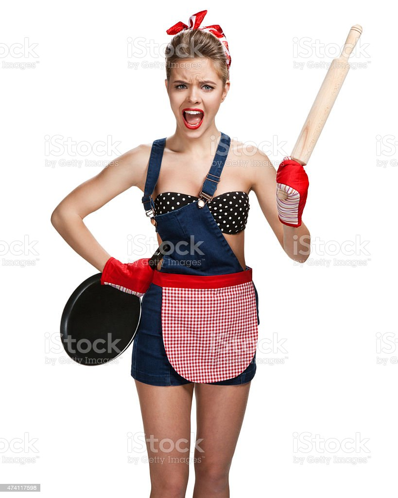 Shrewish maid wearing apron with wooden rolling pin stock photo