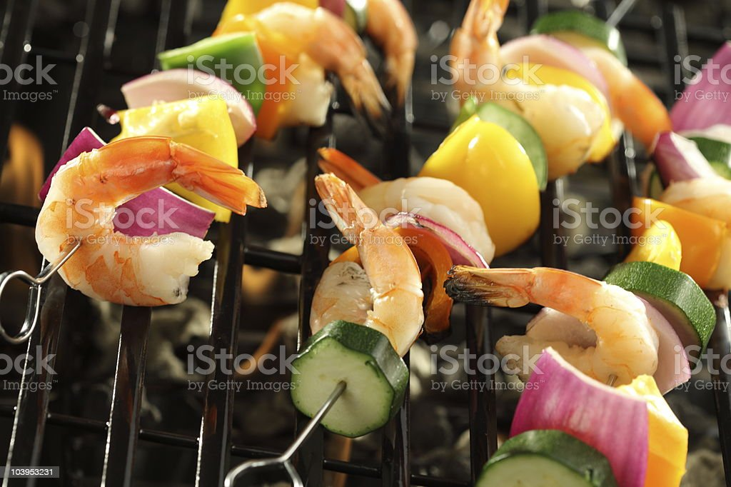 Shrimp and vegetable skewers cooking on grill royalty-free stock photo