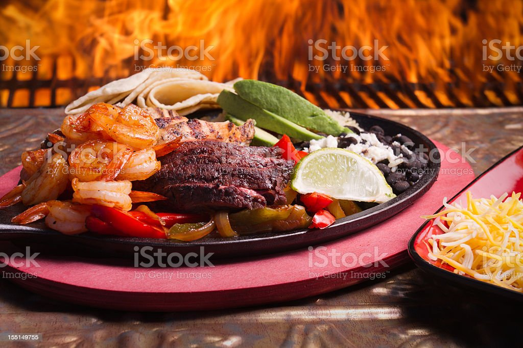 Shrimp, Beef and Chicken Fajitas with Flames royalty-free stock photo