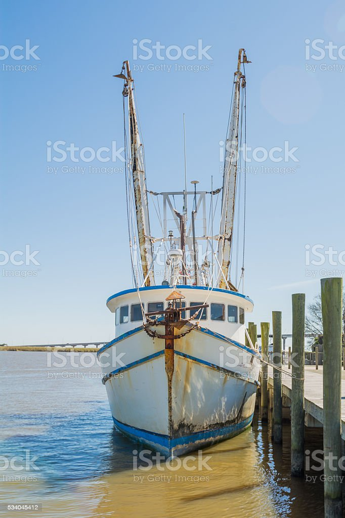 Shrimp boat tied to pier stock photo