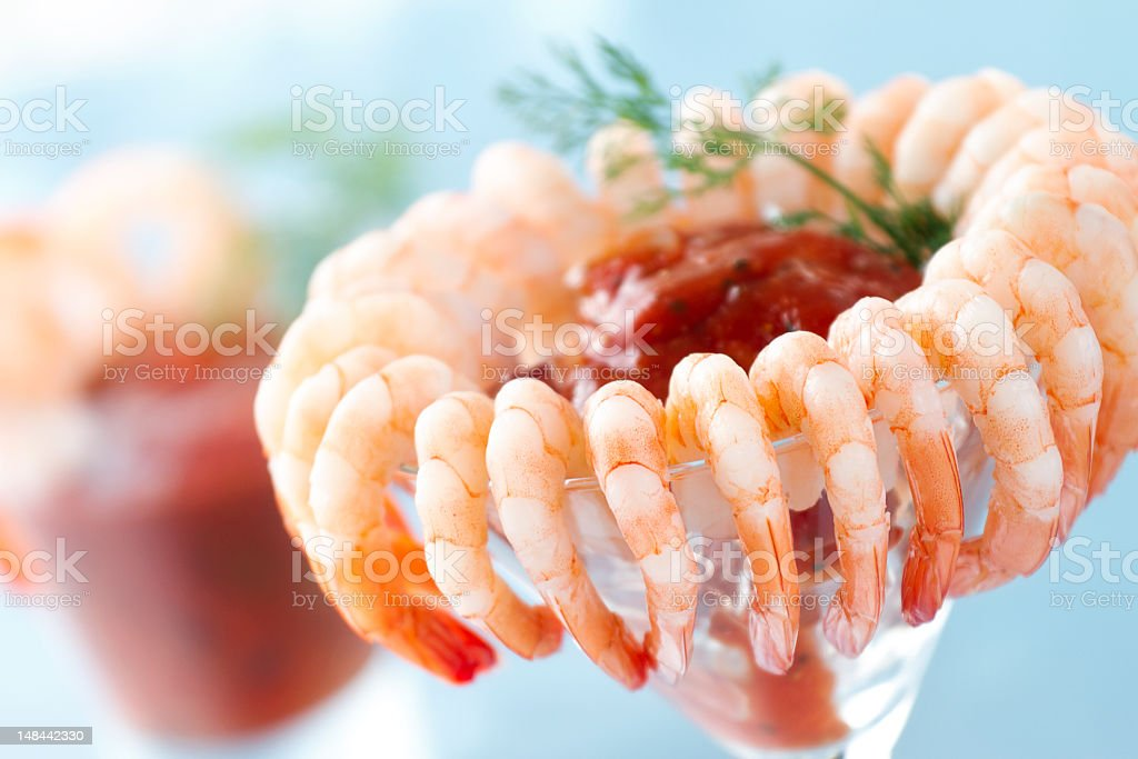 Shrimp cocktail closeup with blurred cocktail in background stock photo