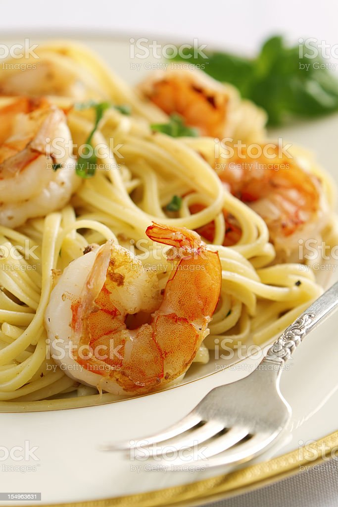 Shrimp scampi and linguine on a white plate with metal fork stock photo
