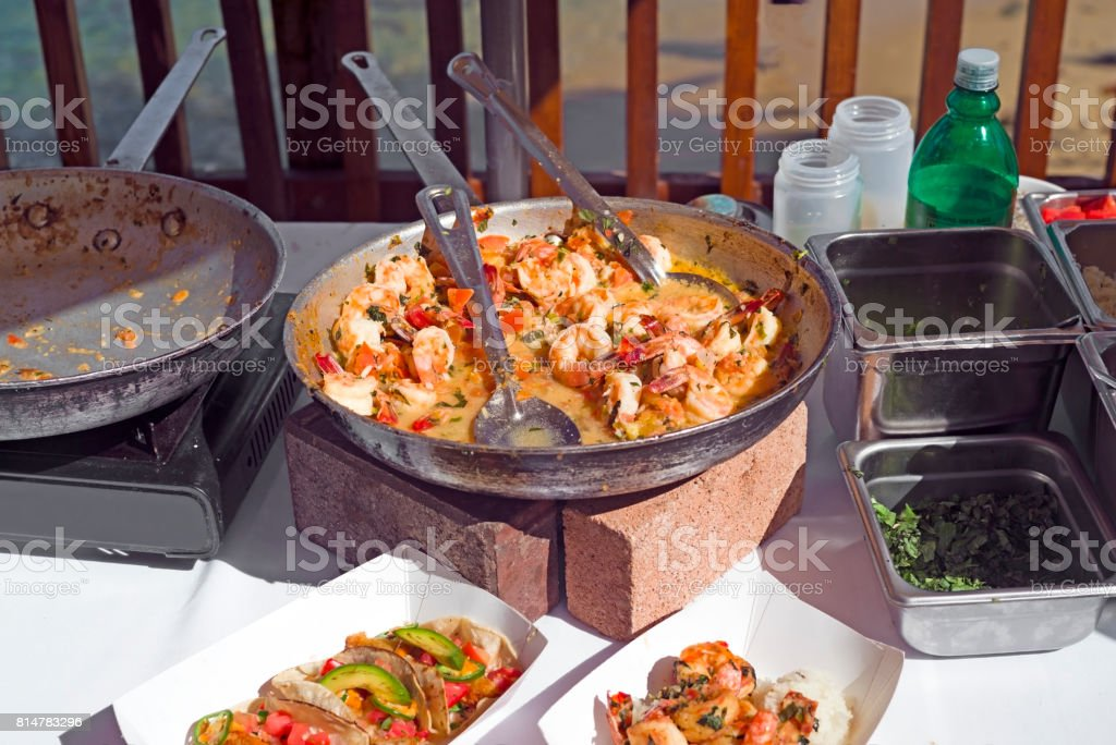 Shrimp scampi street food cooking setup with frying pans, ingredients and utensils. stock photo