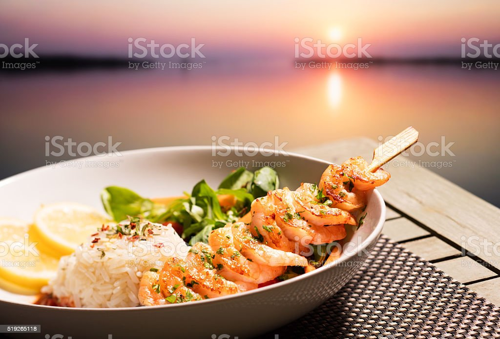 Shrimp skewers and sunset stock photo