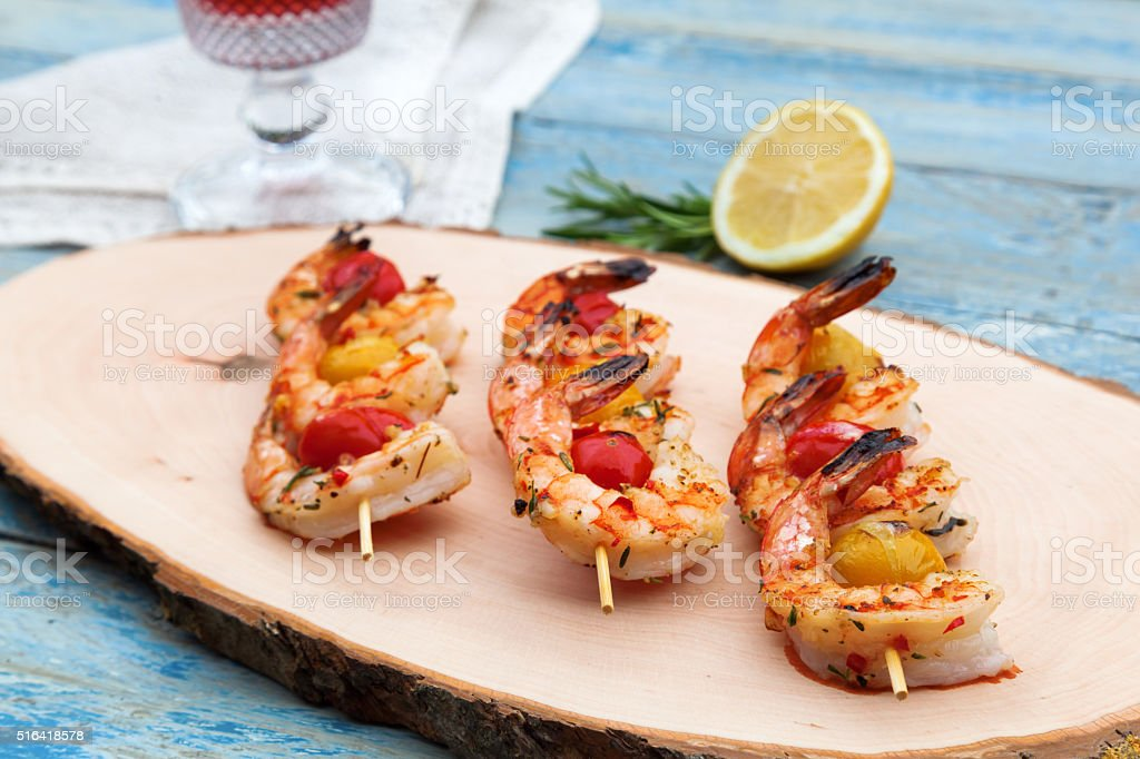 shrimp skewers on a wooden board stock photo