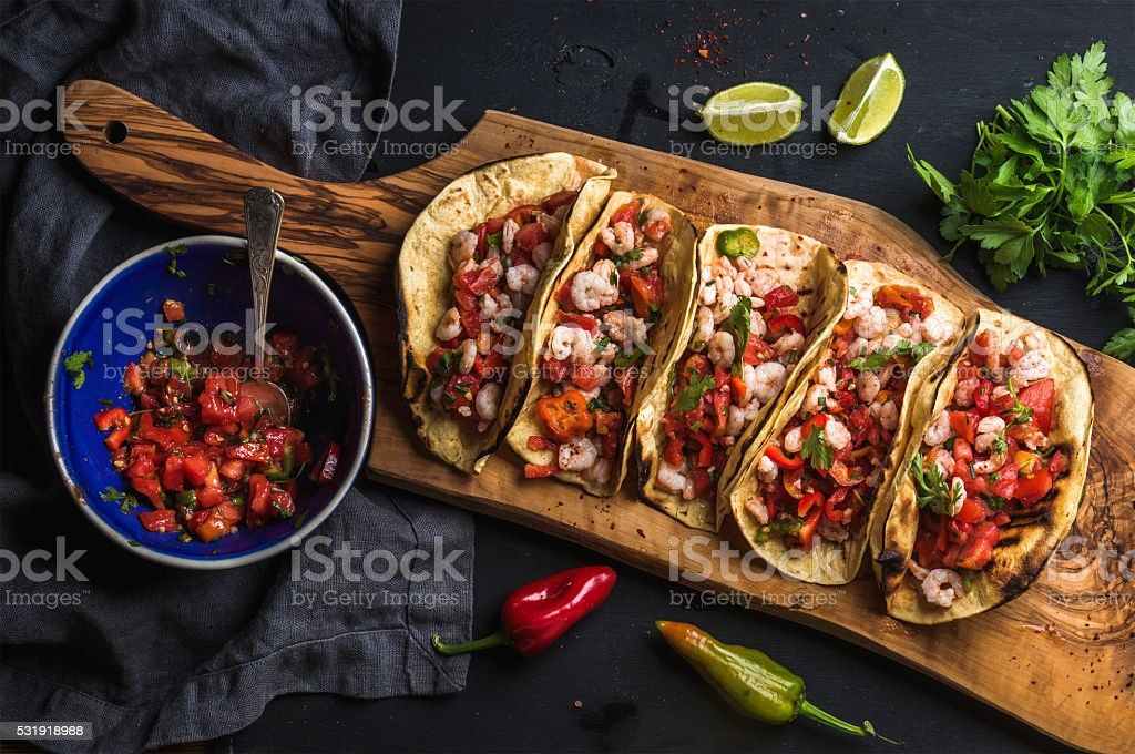 Shrimp tacos with homemade salsa, limes and parsley stock photo