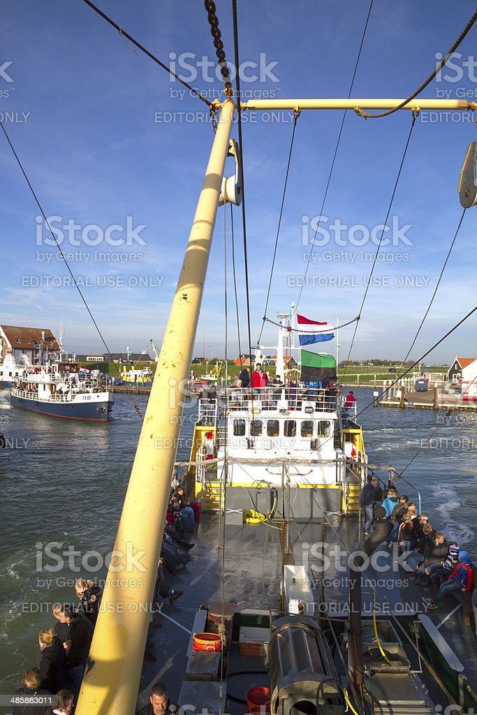 Shrimp trawler with touristical fishing passengers leaving harbour stock photo