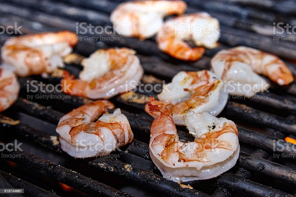 Shrimps getting grilled on barbecue stock photo