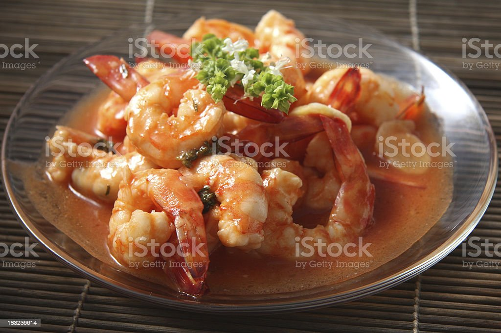 Shrimps in tomato garlic sauce with basil flowers royalty-free stock photo