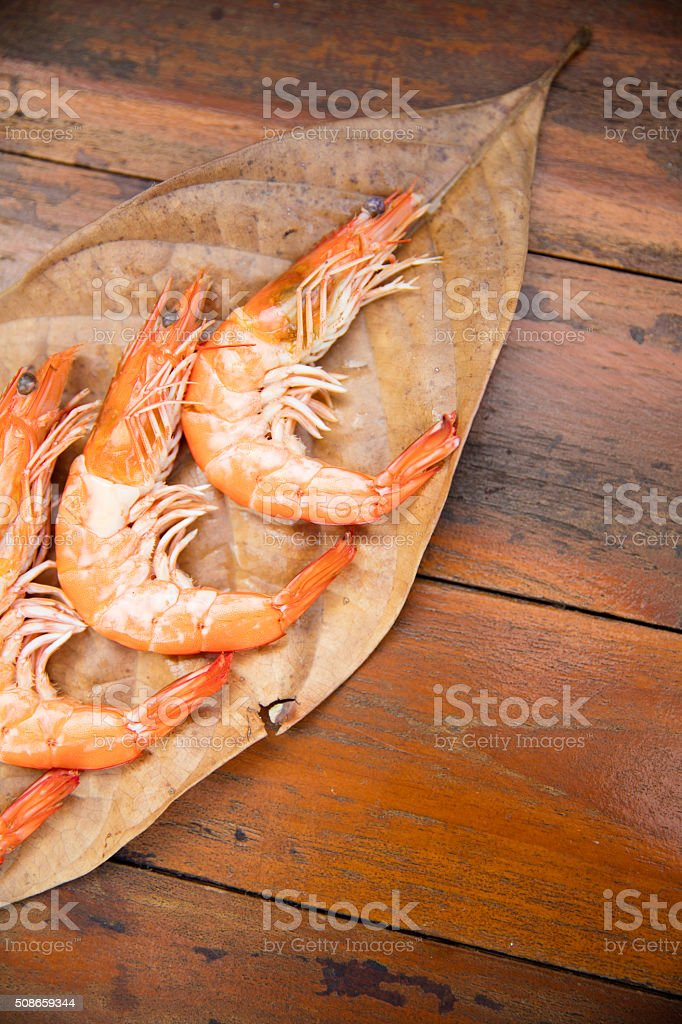 shrimps on a dry leaf on a wooden table stock photo
