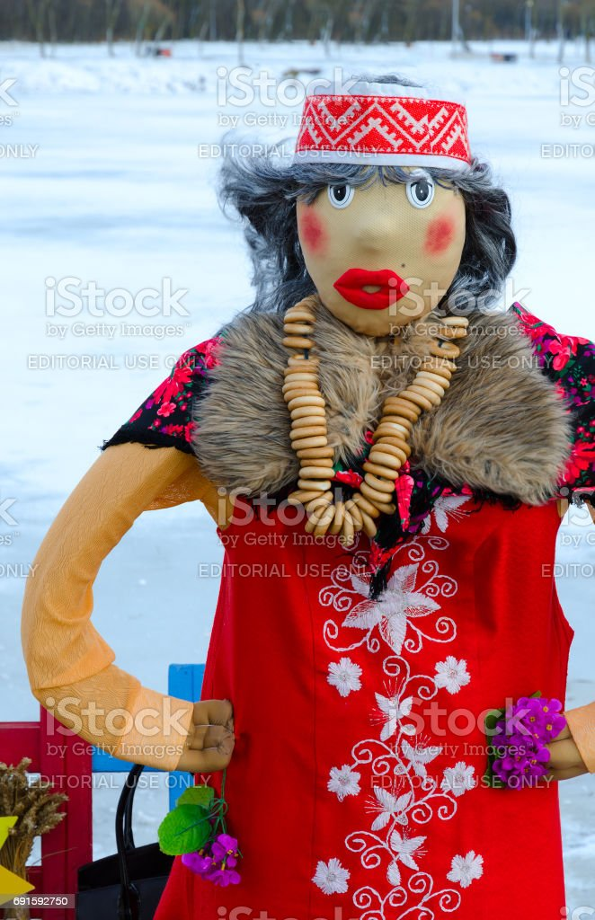 Shrovetide doll in red sundress with embroidery and colorful shawl with bunch of bagels on neck at Shrovetide festivities stock photo