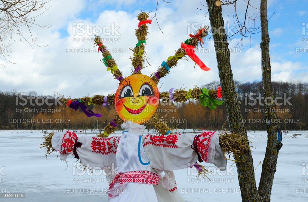 Shrovetide doll with face as sun and straw braids in form of sun rays on background of spring landscape stock photo