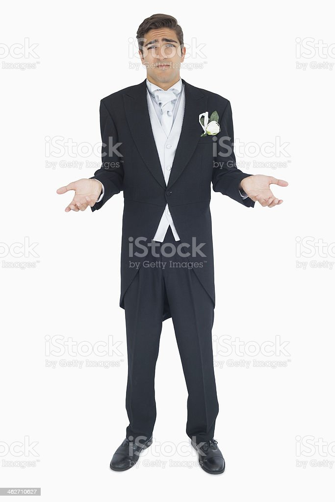 Shrugging attractive young groom looking at camera stock photo