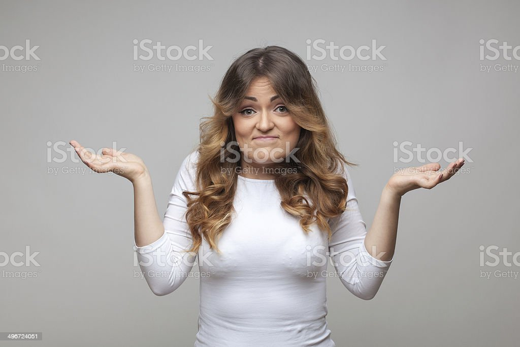 Shrugging woman in doubt doing shrug stock photo