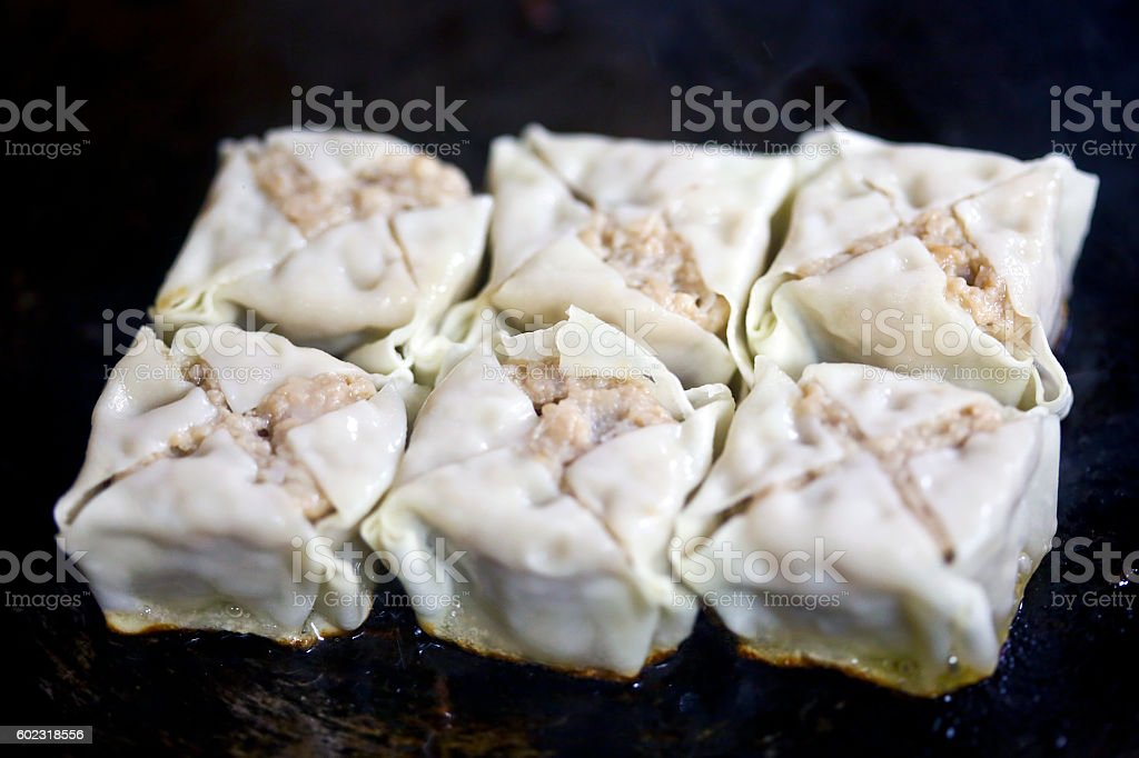 Shumai being cooked in frying pan stock photo