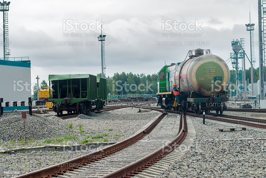 Shunting locomotive transports tank on other way stock photo