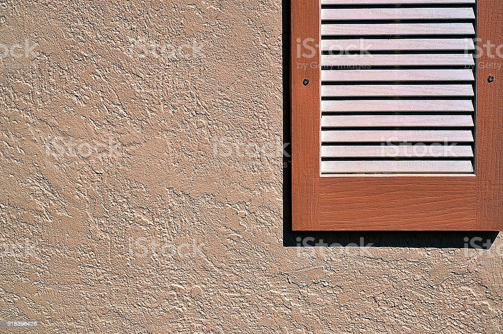 Shutter on exterior stucco wall stock photo