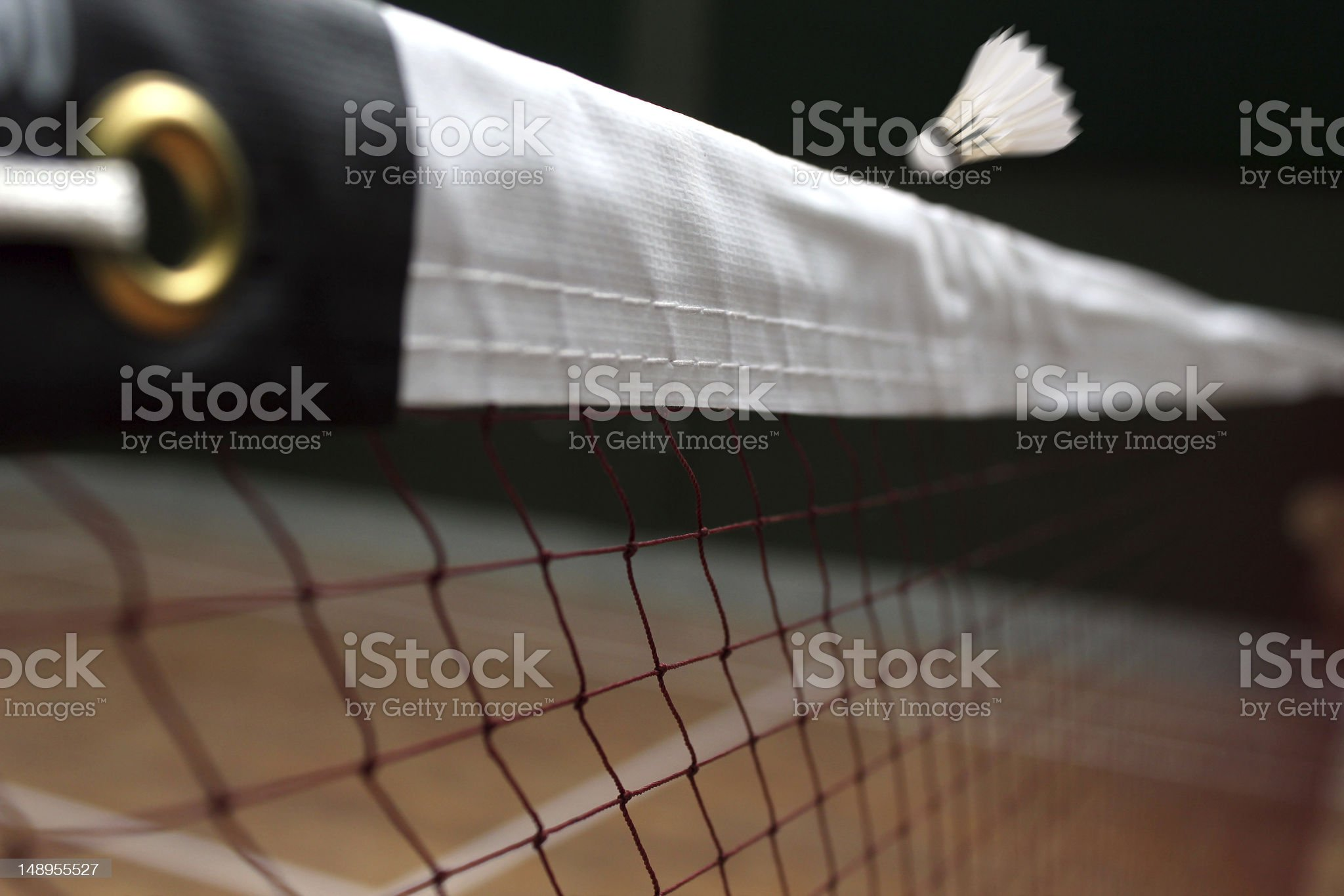 Shuttle badminton net up close and a fast moving shuttlecock royalty-free stock photo