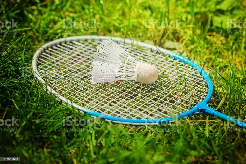 Shuttlecock and badminton racket on green grass stock photo