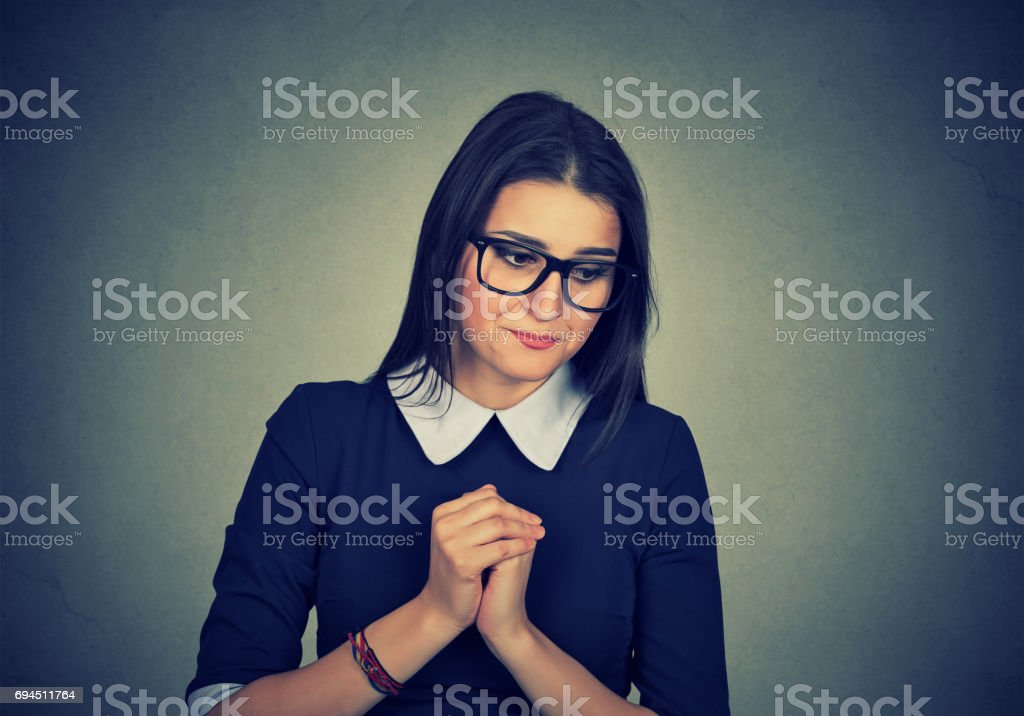 Shy anxious woman looking down stock photo