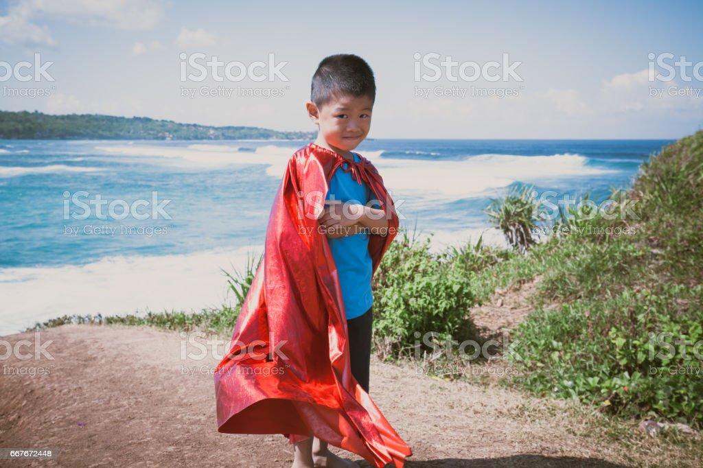 Shy boy dressed as superhero stock photo