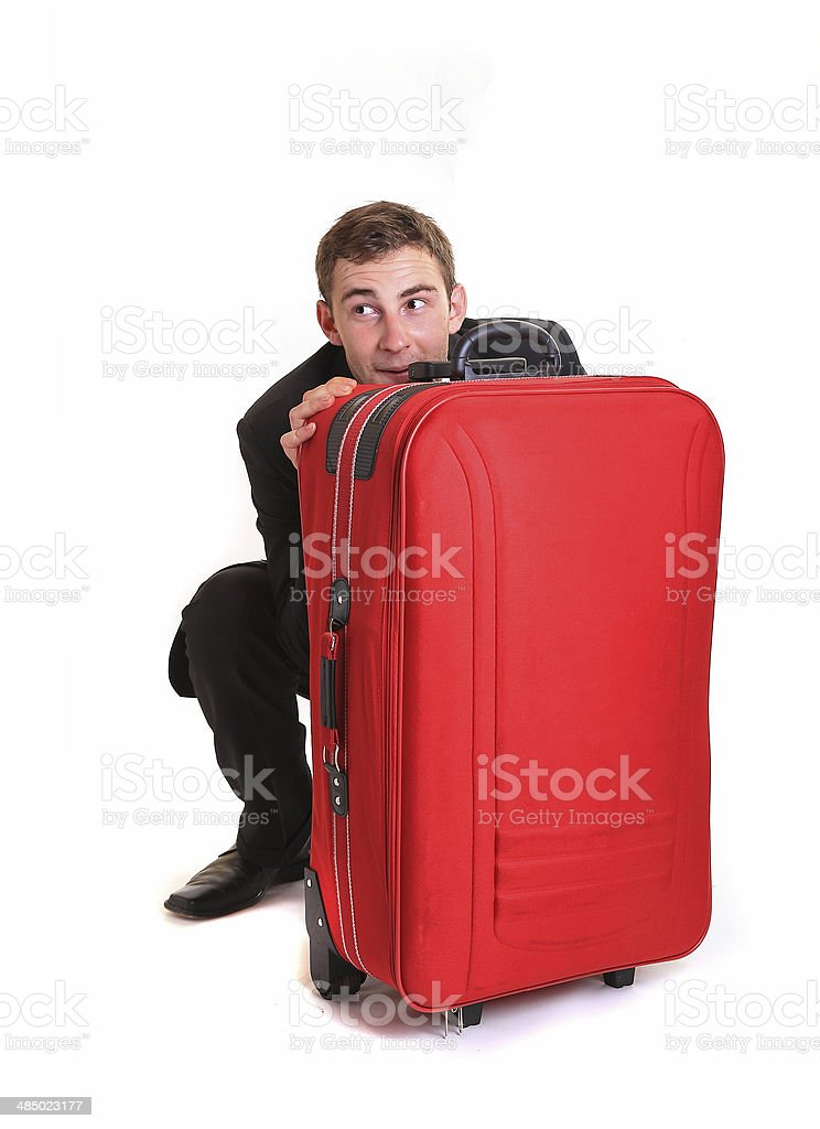 Shy business man hide behind red luggage stock photo