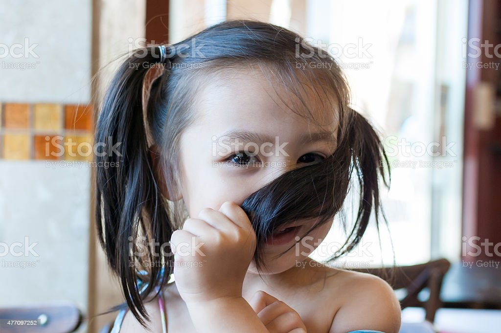 Shy little girl covering her face with her hair stock photo