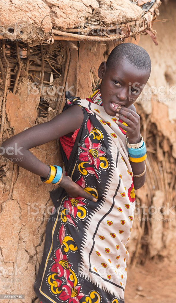 Shy Maasai girl in front of hut. Traditional kanga. stock photo