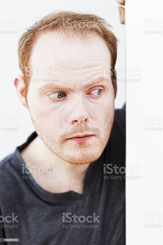Shy man peeking around wall stock photo