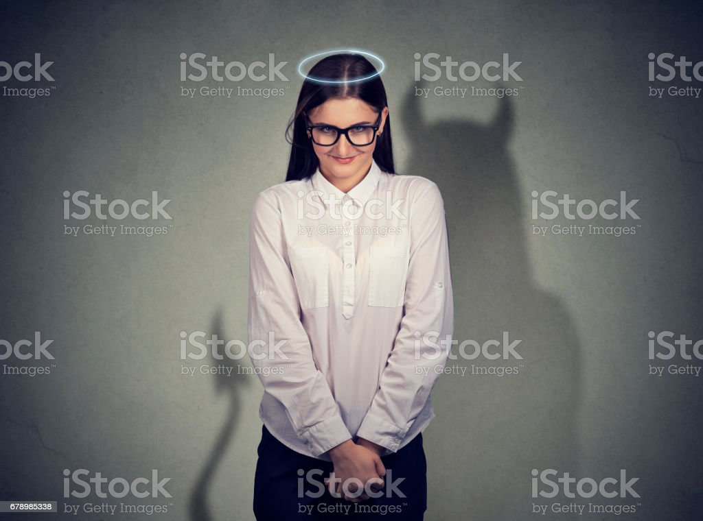 Shy quiet angel woman with devil character stock photo