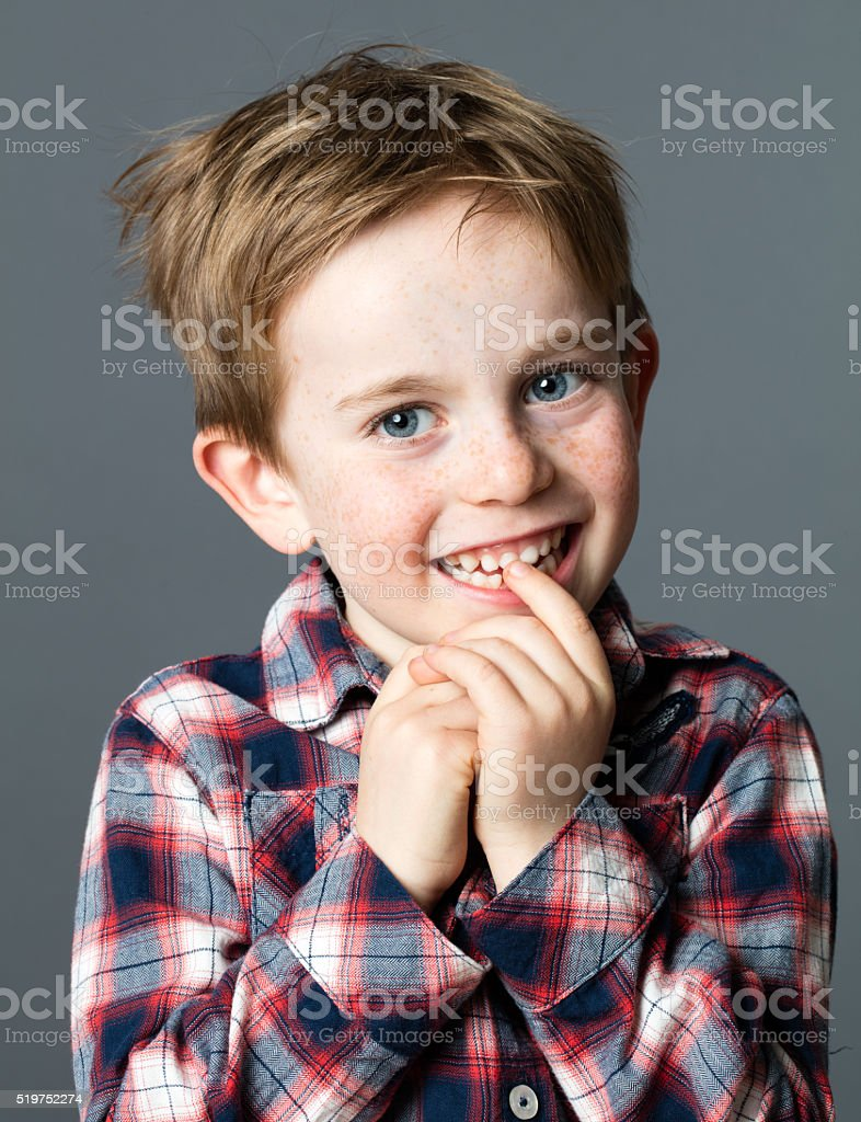 shy red hair young old boy smiling and biting teeth stock photo