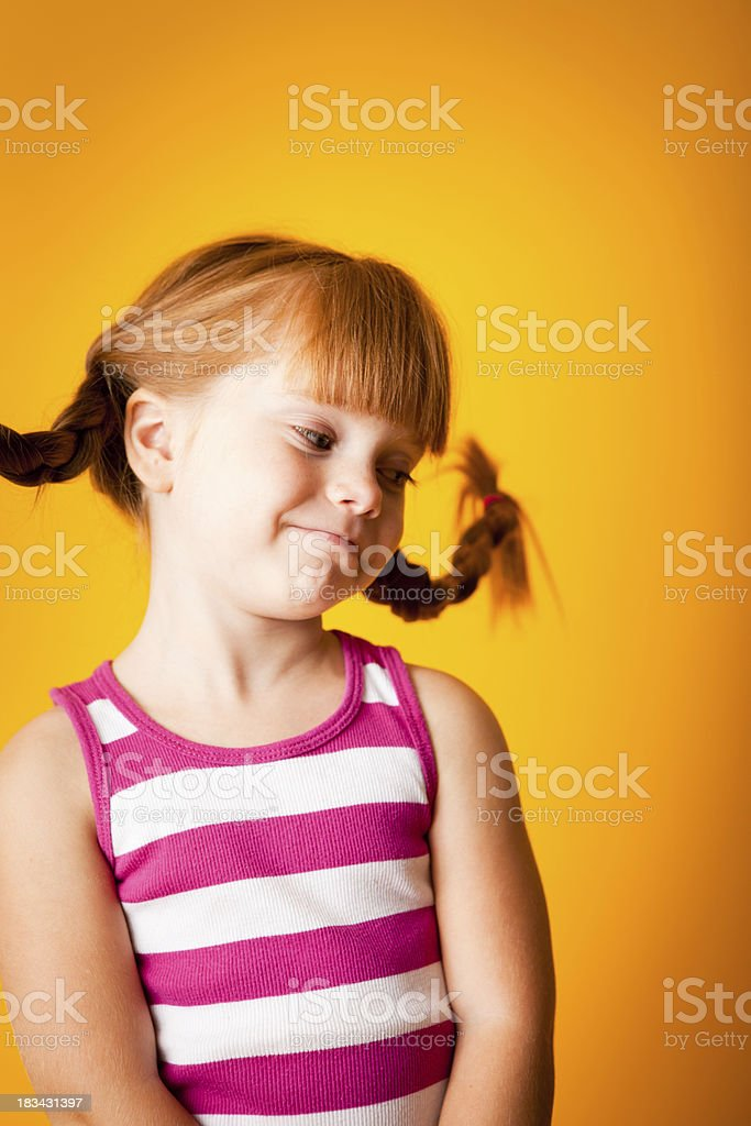 Shy, Red-Haired Girl with Upward Braids and a Smirk royalty-free stock photo