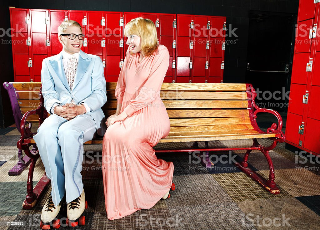 Shy Retro 70's Couple Flirting at the Roller rink royalty-free stock photo