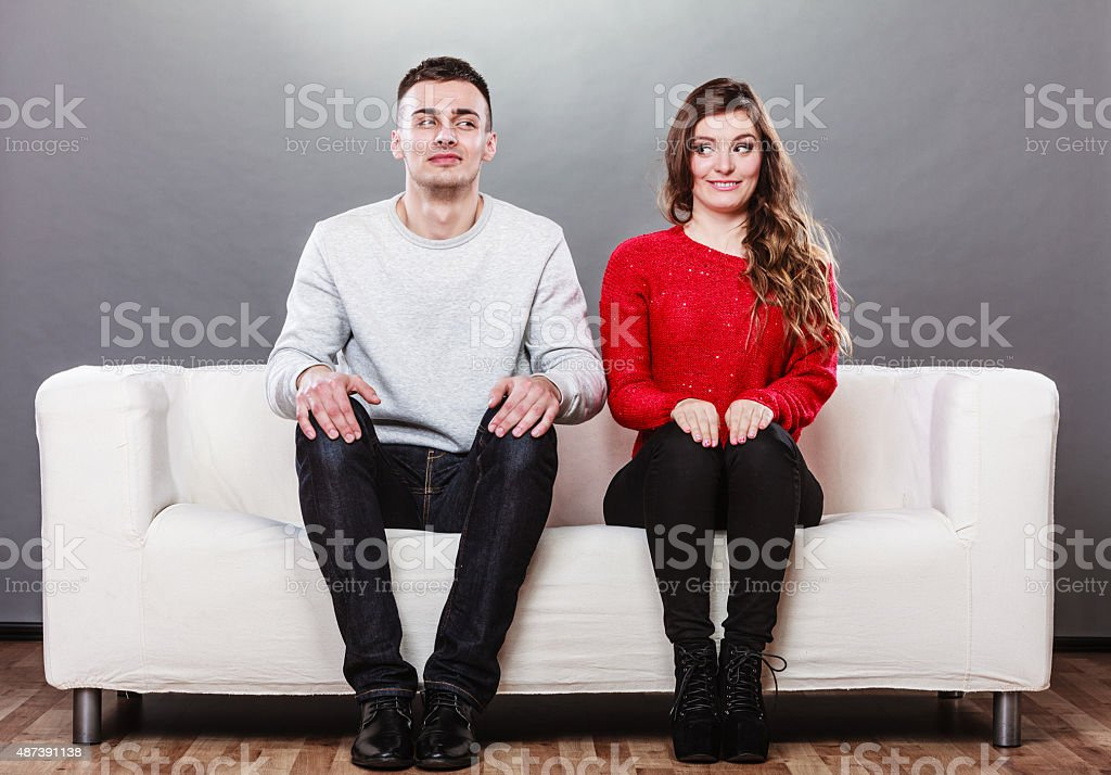 Shy woman and man sitting on sofa. First date. stock photo