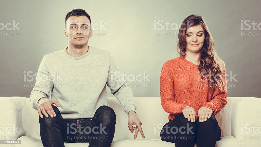 Shy woman and man sitting on sofa stock photo