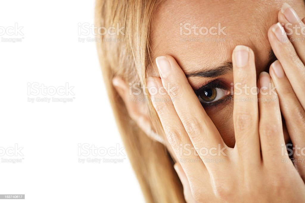 shy woman looking through fingers stock photo