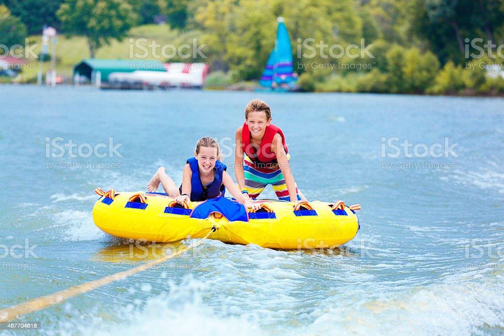 Sibling Children Playfully Tubing over Lake Water, Enjoying Summer Vacation stock photo