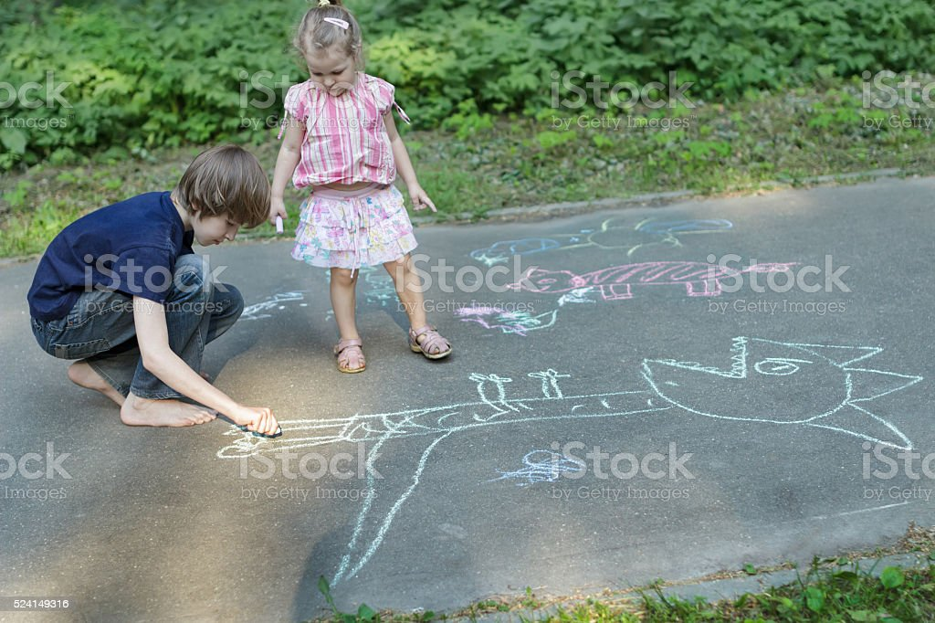 Sibling children sharing sidewalk chalks and drawing on asphalt surface stock photo
